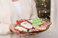 Galletas del pan de jengibre de la Navidad en la placa en las manos del ` s de las mujeres Imagen de archivo libre de regalías