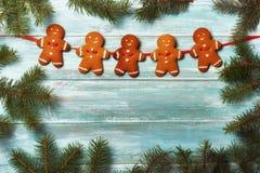 Galletas del pan de jengibre de la Navidad en un viejo tablero rodeado por el abeto Fotografía de archivo libre de regalías