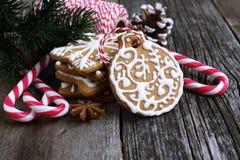 Galletas del pan de jengibre de la Navidad en una tabla de madera con los bastones de caramelo Imagen de archivo