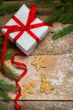 Galletas del pan de jengibre rodeadas por la picea y un regalo para Christma Imagen de archivo