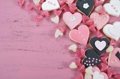 Galletas del rosa de la forma del corazón, blancas y negras y caramelo románticos Fotografía de archivo