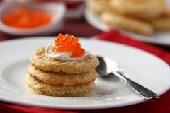 Galletas del salvado de la avena con el caviar y el queso cremoso rojos Foto de archivo libre de regalías
