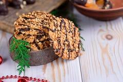 Galletas dulces con los cacahuetes en una placa y las rebanadas anaranjadas en choc Foto de archivo