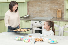 Galletas dulces de la hornada de la muchacha con su madre Fotos de archivo
