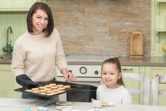 Galletas dulces de la hornada de la muchacha con su madre Imagen de archivo