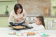 Galletas dulces de la hornada de la muchacha con su madre Imagen de archivo libre de regalías