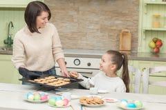 Galletas dulces de la hornada de la muchacha con su madre Fotografía de archivo libre de regalías