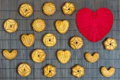 Galletas dulces del azúcar diapositivas en forma de corazón en una siesta de bambú marrón Foto de archivo libre de regalías