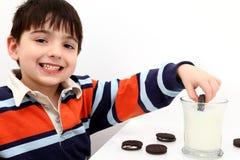 Galletas Dunking del muchacho adorable en leche Fotografía de archivo libre de regalías