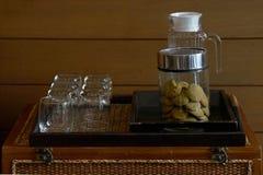 Galletas en el tarro de cristal en la bandeja de madera con los vidrios y la botella para el SE imagenes de archivo