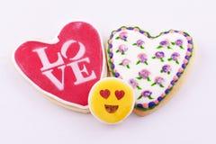 Galletas en forma de corazón con las flores dibujadas y el amor de la palabra Foto de archivo libre de regalías