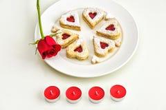 Galletas en forma de corazón hechas en casa de Linzer de la almendra en la placa blanca Aniversario del ffor de las rosas rojas d Imagenes de archivo