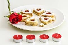 Galletas en forma de corazón hechas en casa de Linzer de la almendra en la placa blanca Aniversario del ffor de las rosas rojas d Imagen de archivo libre de regalías