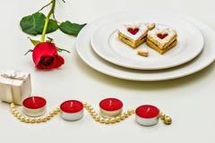 Galletas en forma de corazón hechas en casa de Linzer de la almendra en la placa blanca Aniversario del ffor de las rosas rojas d Fotos de archivo