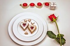 Galletas en forma de corazón hechas en casa de Linzer de la almendra en la placa blanca Aniversario del ffor de las rosas rojas d Imágenes de archivo libres de regalías