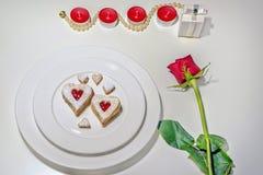 Galletas en forma de corazón hechas en casa de Linzer de la almendra en la placa blanca Aniversario del ffor de las rosas rojas d Foto de archivo libre de regalías