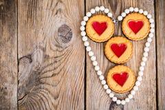 Galletas en forma de corazón en la tabla de madera fotos de archivo
