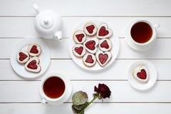 Galletas en forma de corazón para el día de tarjetas del día de San Valentín con la tetera, dos tazas de té y la composición colo Fotografía de archivo