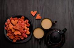 Galletas en forma de corazón rojas, dos tazas de té con leche y tetera El día de tarjeta del día de San Valentín, Copyspace Fotografía de archivo