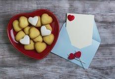 Galletas en forma de corazón y dos velas Imagen de archivo