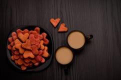 Galletas en forma de corazón rojas y dos tazas de café con leche en una tabla negra Día de tarjeta del día de San Valentín Foto de archivo