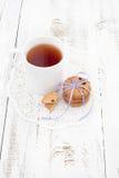 Galletas en una placa blanca con la taza de té Fotografía de archivo libre de regalías