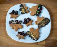 Galletas en una placa blanca, fondo marrón de madera Árbol de navidad o galletas formadas estrellas Imagen de archivo libre de regalías