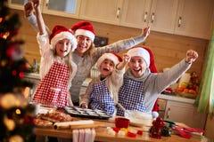 Galletas felices de la hornada de la familia en la Navidad imagen de archivo libre de regalías