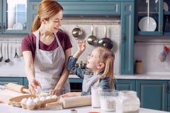 Galletas felices de la hornada de la mujer así como su hija Fotos de archivo libres de regalías