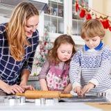 Galletas felices de la Navidad de la hornada de la familia en casa Imagen de archivo libre de regalías