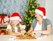 Galletas felices de la Navidad de la hornada de la mamá y de la hija Imagen de archivo libre de regalías