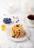 Galletas frescas con los arándanos, mesa de desayuno del jarabe de arce Imágenes de archivo libres de regalías