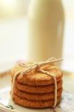 Galletas hechas caseras sanas de la harina de avena y una botella de leche fresca Foto de archivo libre de regalías