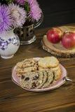 Galletas hechas en casa: coco, harina de avena, chocolate, en una tabla de madera, con un pote del té, en el fondo de una composi foto de archivo