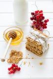 Galletas hechas en casa de la avena con la miel, las pasas rojas, el yogur y la leche Foco selectivo Imagen de archivo