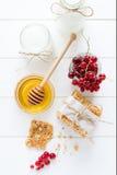 Galletas hechas en casa de la avena con la miel, las pasas rojas, el yogur y la leche Foco selectivo Foto de archivo libre de regalías
