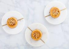 Galletas hechas en casa de la galleta con las nueces de la almendra y la mantequilla de cacahuete en los prácticos de costa de má imagenes de archivo