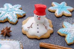 Galletas hechas en casa de la Navidad, muñeco de nieve derretido con la choza roja y pan de jengibre del copo de nieve Imagen de archivo libre de regalías