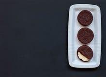 galletas hechas en casa del chocolate en un fondo negro con café Imagen de archivo libre de regalías