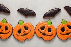 Galletas hechas en casa del jengibre en la forma de las calabazas y palos en Halloween En el fondo concreto más ligero Visión sup imagen de archivo