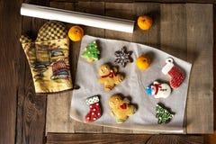 Galletas hechas en casa del pan de jengibre de la Navidad en la tabla de madera foto de archivo