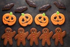 Galletas hechas en casa del pan de jengibre para Halloween bajo la forma de calabazas, hombres de pan de jengibre y palos en fond Fotografía de archivo libre de regalías