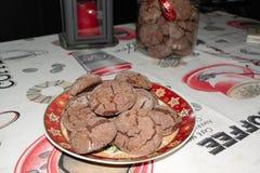 Galletas hechas en casa deliciosas de la Navidad del cacao y un tarro y una vela en la parte posterior imágenes de archivo libres de regalías