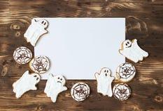 Galletas hechas en casa deliciosas divertidas del jengibre para Halloween en la tabla y la hoja de madera oscuras del papper Visi Fotos de archivo libres de regalías