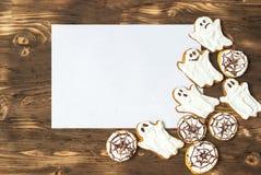 Galletas hechas en casa deliciosas divertidas del jengibre para Halloween en la tabla y la hoja de madera oscuras del papper Visi Foto de archivo