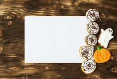 Galletas hechas en casa deliciosas divertidas del jengibre para Halloween en la tabla y la hoja de madera oscuras del papper Visi Imagen de archivo