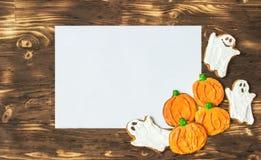 Galletas hechas en casa deliciosas divertidas del jengibre para Halloween en la tabla y la hoja de madera oscuras del papper Visi Imágenes de archivo libres de regalías