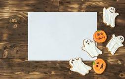Galletas hechas en casa deliciosas divertidas del jengibre para Halloween en la tabla y la hoja de madera oscuras del papper Visi Imagen de archivo libre de regalías