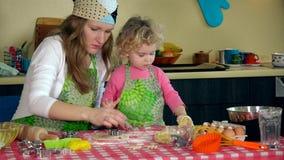 Galletas hechas en casa hechas por la mujer feliz con la hija en la tabla almacen de metraje de vídeo