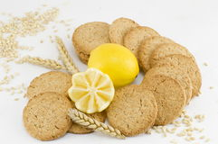 Galletas integrales y limón adornado en el fondo blanco Fotografía de archivo libre de regalías